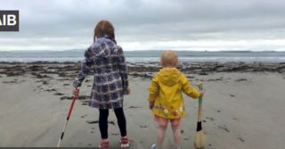 two children with their back to the camera looking out at the sea on a sandy beach