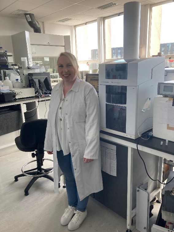 Blonde woman standing in a lab wearing a white lab coat