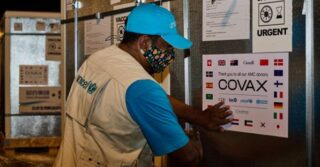 UNICEF worker with blue Unicef cap and beige vest puts up vaccination signage